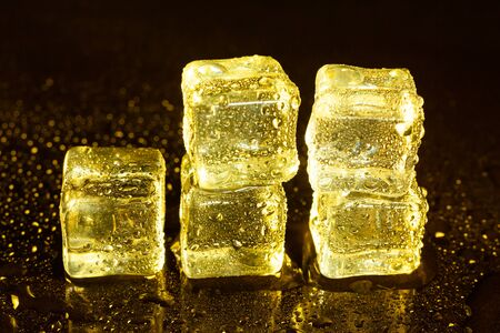 ice cubes on a reflections yellow light. Stok Fotoğraf