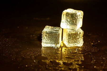 ice cubes on a reflections yellow light. Banque d'images - 131781357
