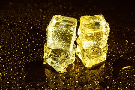 ice cubes on a reflections yellow light. Banque d'images - 131781317