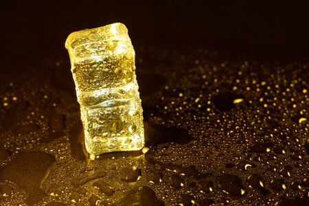 ice cubes on a reflections yellow light. Banque d'images - 131780704