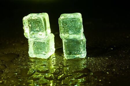 Green ice cubes on black table background. Banque d'images - 131780458