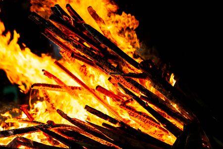 Feu de joie qui brûle sur fond sombre, flamme au bois.