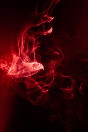 Mouvement de fumée rouge sur fond noir.