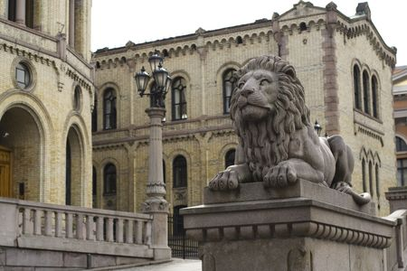 oslo: Sculpture of Lion with the Norwegian Parliament building in background. Oslo city