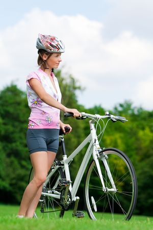 Pretty girl standing with a bicycle photo