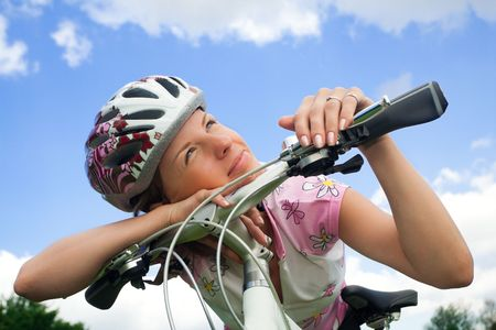 Healthy young girl with bicycle looking at the sun photo