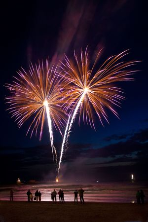 Spectators standing on the beach and looking at fireworks
