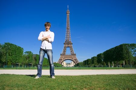 Young man standing on the Champs de Mars. Eiffel tower in background