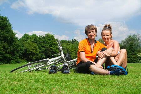 Happy young couple resting on a green meadow after bicycle trip photo