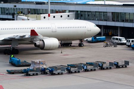 cargo service: Aircraft standing at gate and being loaded with luggage Stock Photo