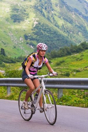 Young girl on a bicycle moving up to a hill Stock Photo