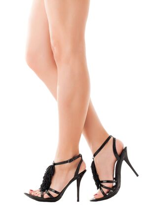 Elegant legs of a young woman wearing black shoes. Isolated over white photo