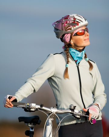 velo: Active young woman with her bicycle. Smiling and looking at the sun