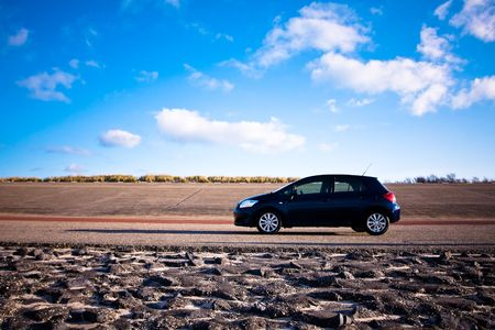 car side: Blue car standing on road. Side with with vibrant sky as background Stock Photo