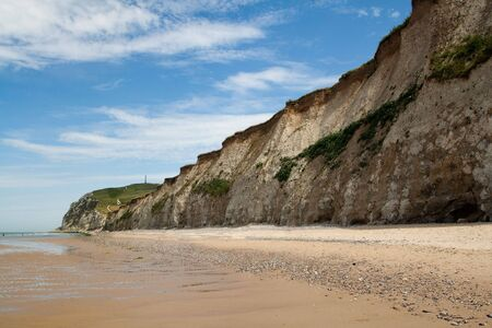 White cliffs and sand beach on the sea shore. The coastline of France