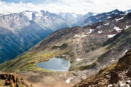 austrian: Lake in form of a heart high in the mountains. Austrian Alps