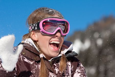 Laughing happy girl on winter sport vacation. Wearing ski mask photo