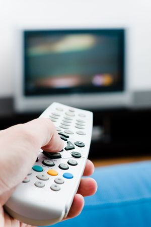 Switching the channels. Hand with remote TV control photo
