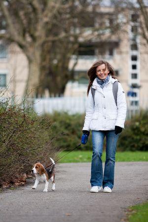 Chica caminando con su perro en la correa. Cachorro Beagle  Foto de archivo