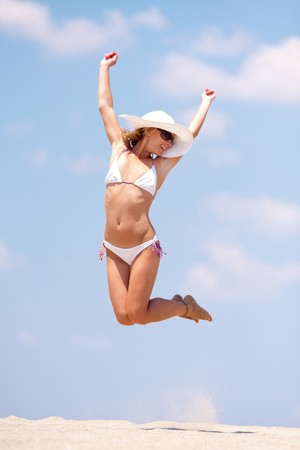Young woman having fun on a beach. Jumping photo