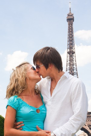 young couple hugging kissing: Lovely couple in Paris with Eiffel tower in background