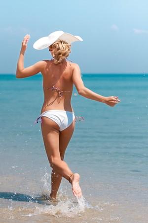 Young woman in bikini running on the beach Stock Photo