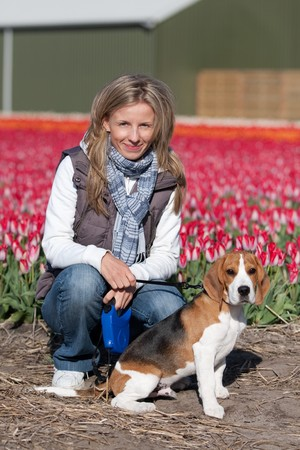 Young woman walking with her beagle dog on flower fields photo