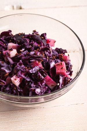 organic flax seed: Healthy red cabbage salad on white wooden background