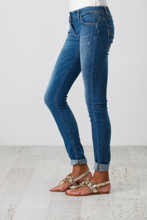 Woman in blue skinny jeans on the white background