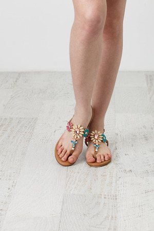 woman sandals: Woman feet in summer shoes on the white wooden floor Stock Photo