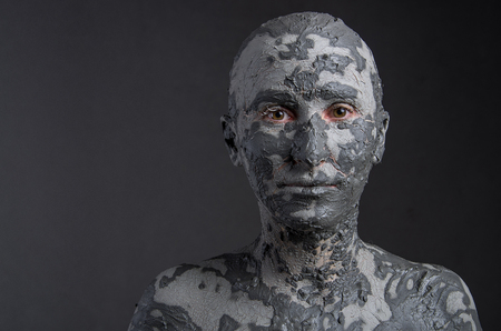 guise: Statuesque woman in clay. Woman covered in clay. Spa treatment or Halloween mask