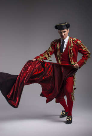capote: Studio shot of a man dressed as Spanish torero, matador, bullfighter. Performing a traditional classic bullfight, standing and holding the capote. Stock Photo