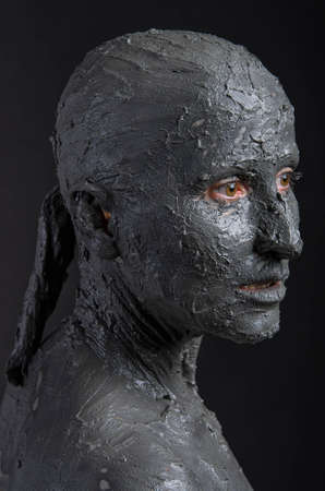 guise: Statuesque woman in wet clay. Woman covered in wet clay. Spa treatment or scary Halloween mask?