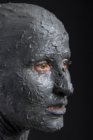 halloween mask: Statuesque woman in wet clay. Woman covered in wet clay. Spa treatment or scary Halloween mask?