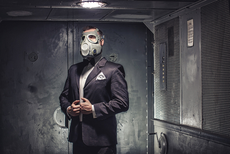 secret agent: Man in gas mask and suit, standing in old elevator. Secret agent, terrorist or businessman of apocalypse? Stock Photo