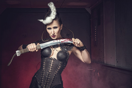 Beautiful warrior woman. Fantasy fighter. Princess or queen in leather corset ready for war. Red and white light weapon. Stock Photo