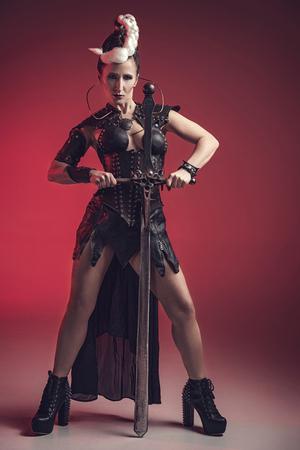 Hermosa mujer guerrera. Fantasía de combate. Princesa o reina en el corsé de cuero listo para la guerra. arma ligera de color rojo y blanco. Foto de archivo