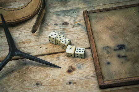 Roman bone dice on a table, by a wax writing tablet. Editorial