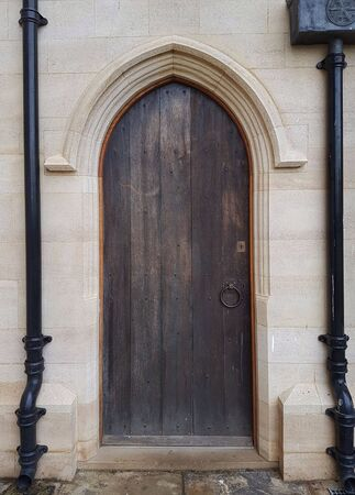 A side door of a church, flanked by old iron drainpipes.