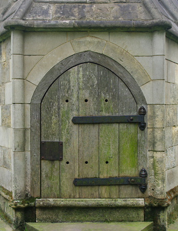A small wooden Gothic door with large iron hinges, in a stone wall. Stock Photo