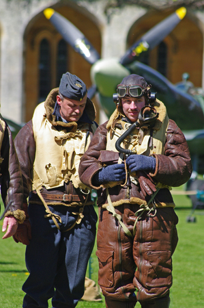Lincoln, England - May 07, 2018: Two men dressed as WW 2 Pilots stand in front of a Spitfire at an event celebrating 100 years of military flying