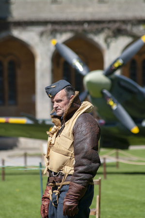 Lincoln, England - May 07, 2018: A man dressed as WWII Pilot stands in front of a fighter plane at an event celebrating 100 years of military flying