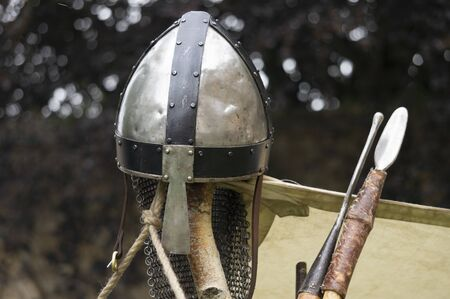 A knights helmets rests atop a post alongside two spears.