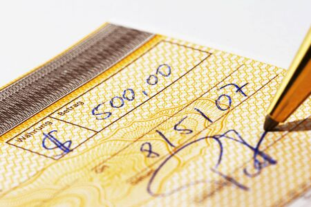Writing a bank check with a pen photo