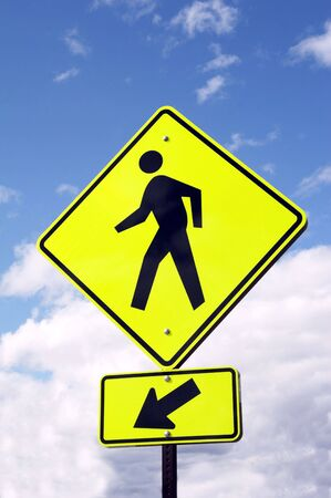 light yellow sign - WATCH PEDESTRIANS on blue sky