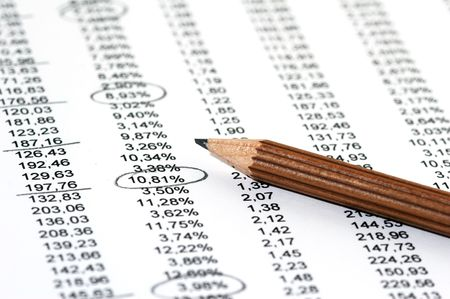 Sales Report in listform with marked data and brown pencil photo
