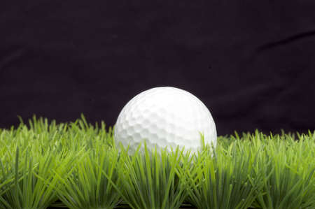 white golfball on green fairway, isolated on black background Stock Photo