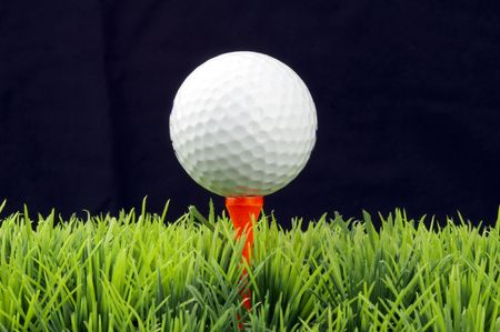 white golfball in orange tee, green fairway, isolated on black background photo