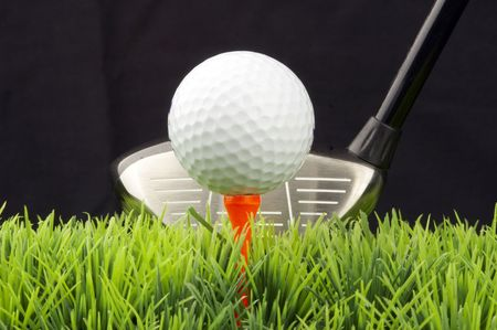 white golfball on tee, driver behind, isolated on black background photo