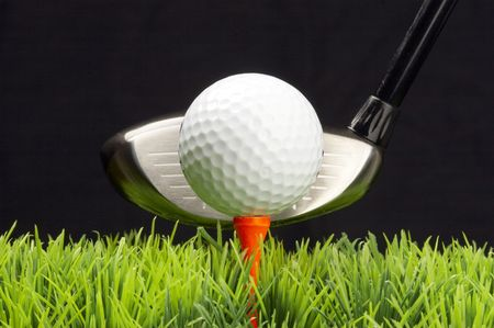 dimple: white golfball on tee, driver behind, isolated on black background Stock Photo